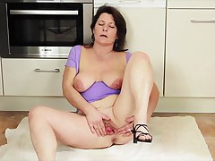 Paulana is a brunette mature lady and she can not think of passing a day without good masturbation. After revealing her nice big boobs with hard nipples on them she spreads white thighs right at the kitchen to rub her large pussy so that she can make it wet and enjoy her desired fingering.